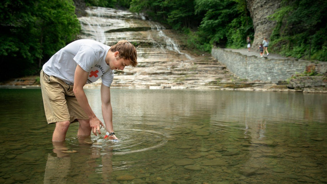 Nate Barott '20, one of five undergraduates on associate professor Ruth Richardson's research team, collects a water sample in June at Buttermilk Falls State Park in Ithaca. The sample was tested using the Biomeme two3 smartphone-enabled PCR thermocycler device.
