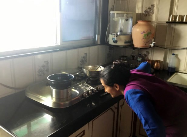A woman tests the students' product while cooking