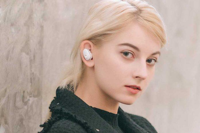 A girl wearing Mugo Pro earbuds