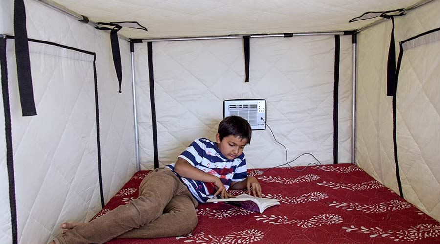A boy reading book inside the Tupik AC tent