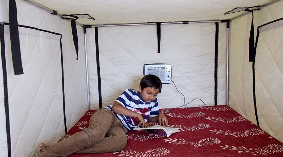 A boy reading book inside the Tupik AC tent