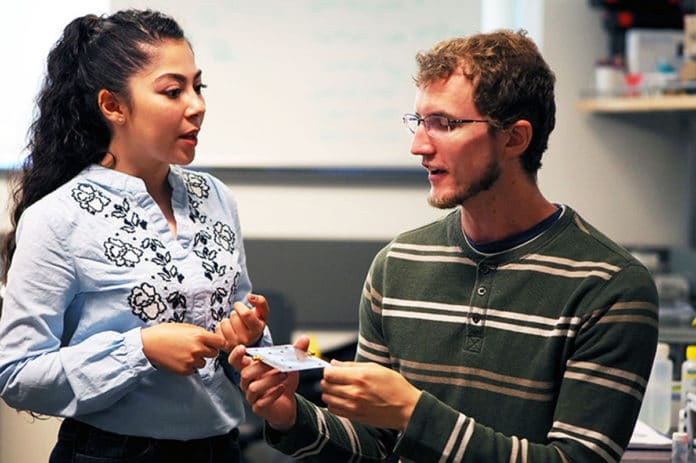 UBCO graduate students Kiana Mirshahidi and Ben Wiltshire demonstrate how small and portable the tiny ice detection senor is. Image Credit: UBC