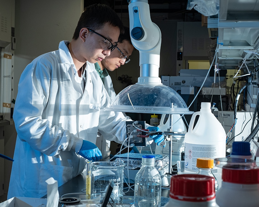 Rice postdoctoral researchers adjust their electrocatalysis reactor to produce liquid formic acid from carbon dioxide. Credit: Rice University