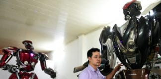 "A new robot-model next to ""Robot-One"", made from spare motorcycle parts, at a workshop in Hanoi.A new robot-model next to ""Robot-One"", made from spare motorcycle parts, at a workshop in Hanoi."