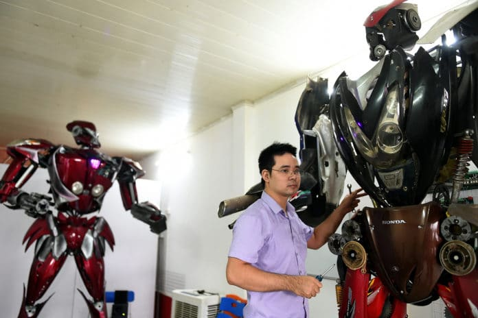 """A new robot-model next to """"Robot-One"""", made from spare motorcycle parts, at a workshop in Hanoi.A new robot-model next to """"Robot-One"""", made from spare motorcycle parts, at a workshop in Hanoi."""