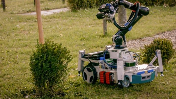 Trimbot robot trimming a bush.