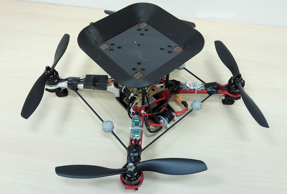 The flying batteries land on a tray mounted atop the main drone and align their legs with electrical contacts. Credit: UC Berkeley