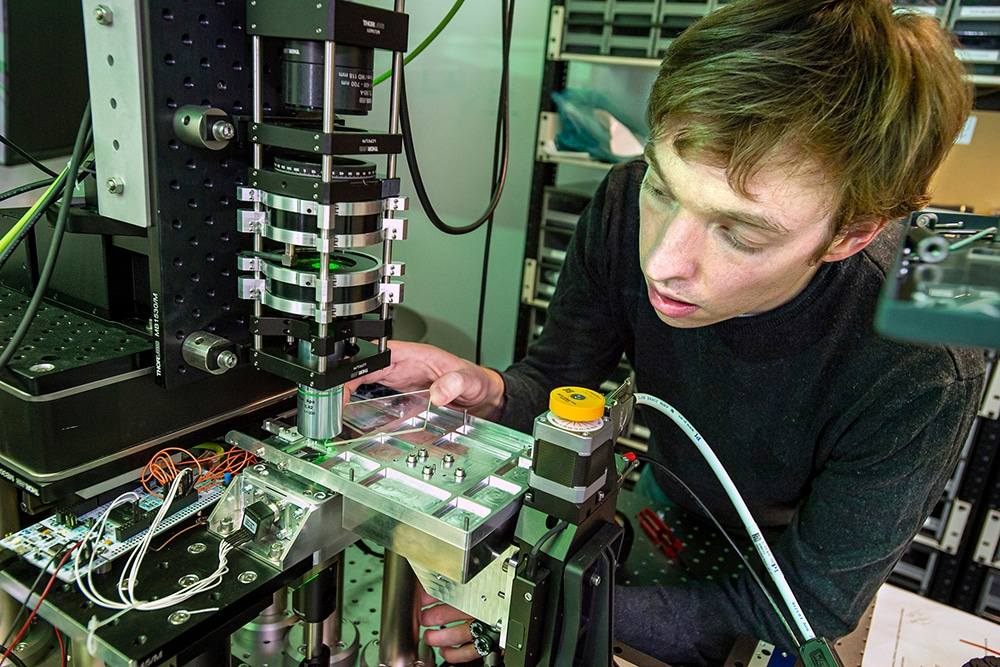 Microsoft senior optical scientist James Clegg loads a piece of glass into a system that uses optics and artificial intelligence to retrieve and read data stored on glass. Credit: Microsoft.