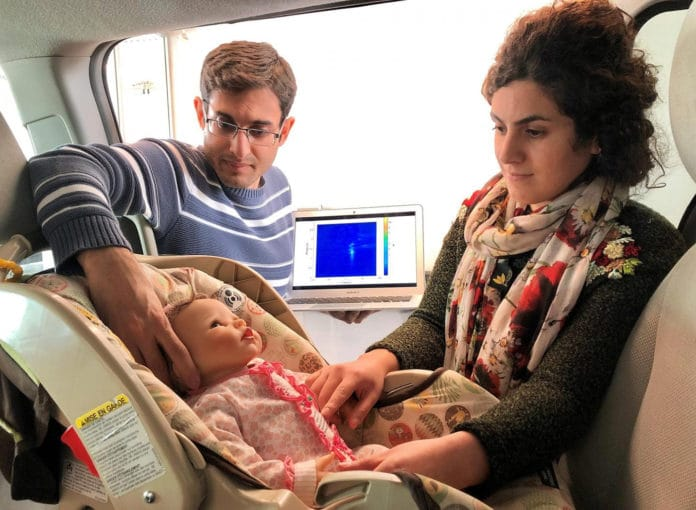 Graduate students Mostafa Alizadeh, left, and Hajar Abedi position a doll, modified to simulate breathing, in a minivan during testing of a new sensor.