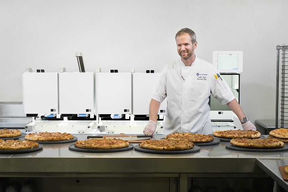 Centerplate Executive Chef Taylor Park stands in front of Picnic's pizza robot at T-Mobile Park, home of the Seattle Mariners.