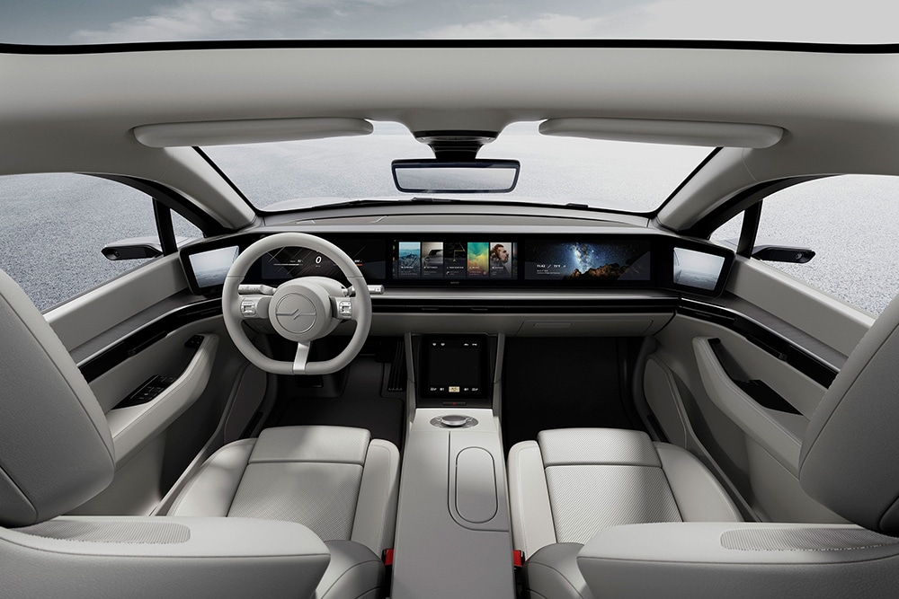 At the front, the occupants look at several large displays that form the dashboard.