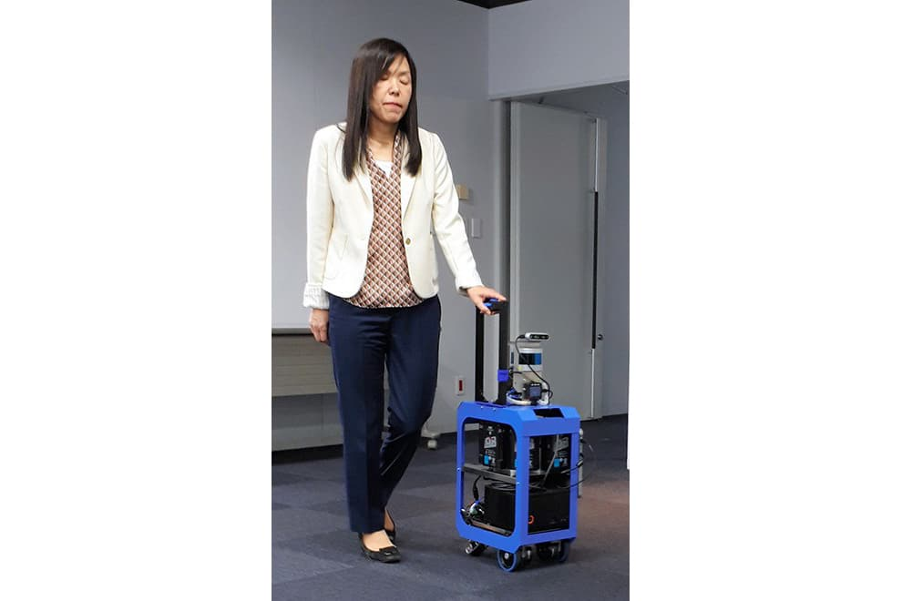 Chieko Asakawa walks with assistance of a robotic suitcase equipped with AI.