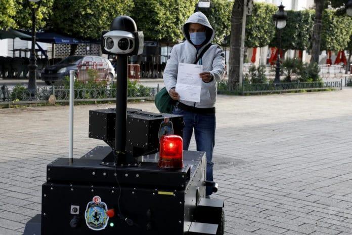 The robot asks to show their IDs and other papers to the its camera.