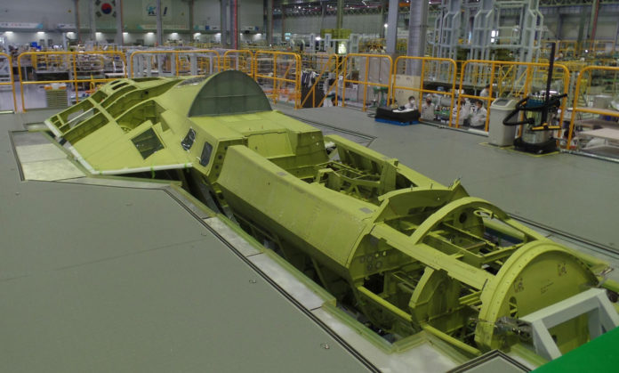 The image shows a partially assembled fuselage of the KF-X fighter prototype.