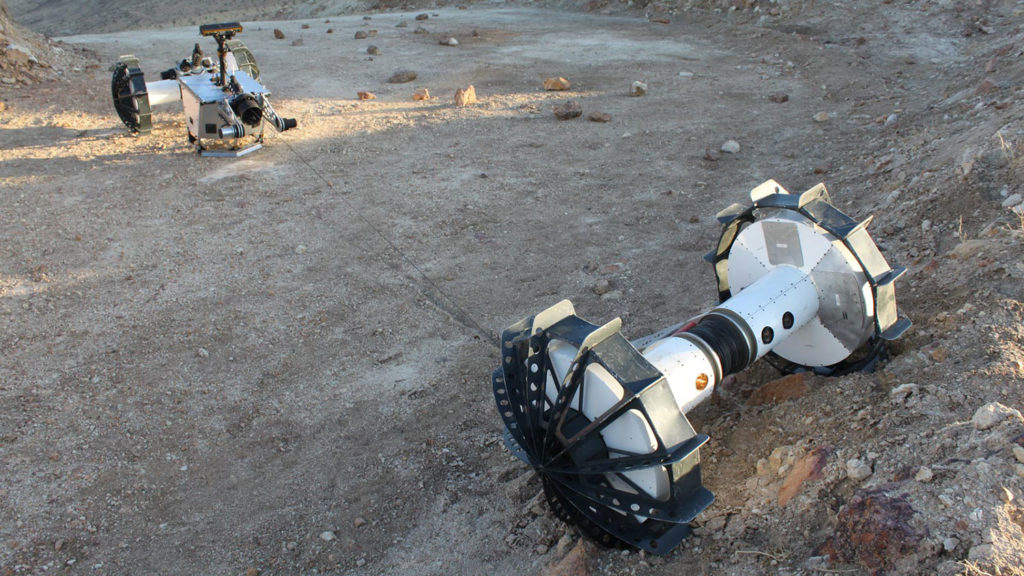 During the same field test, the DuAxel rover separates into two single-axled robots so that one can rappel down a slope too steep for conventional rovers.