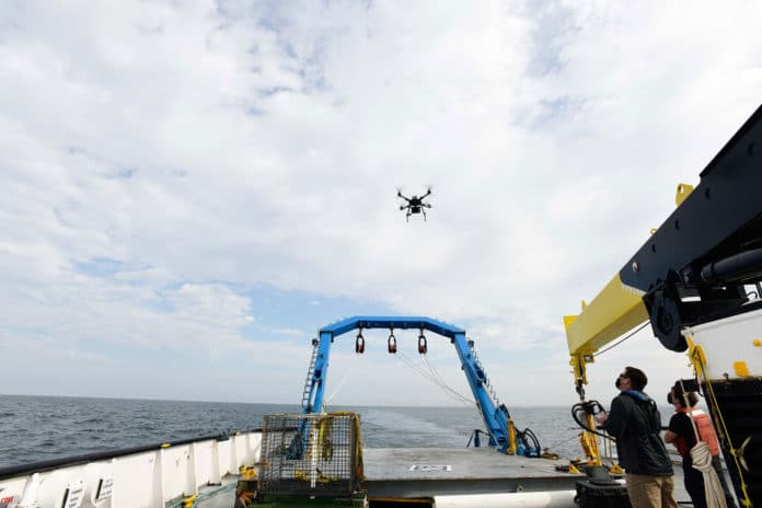 Alan Jaeger and Ian Wilson test out the capabilities of a quadcopter drone at the stern of a ship.
