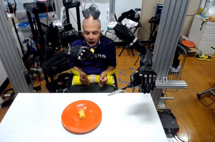 Quadriplegic patient uses brain signals to feed himself with two prosthetic arms.