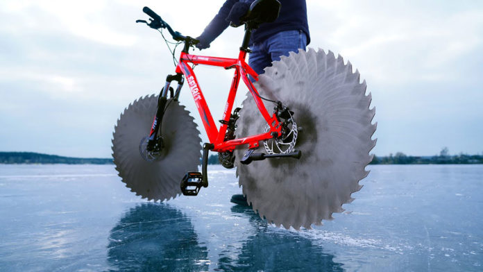An engineer replaces wheels on a bike with circular saws to ride on frozen lake.
