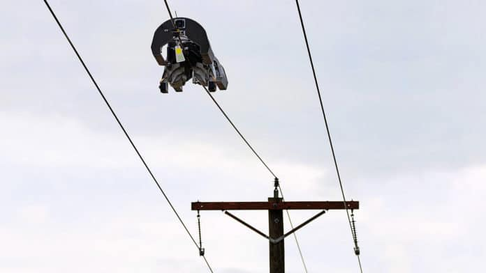 Facebook's Bombyx robot moves along power lines, wrapping them with fiber cable.